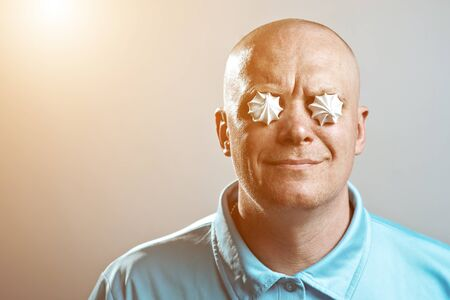 a bald brutal man in a blue shirt put meringues in his eyes