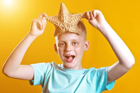 a boy in a light t-shirt holding a starfish on a yellow background