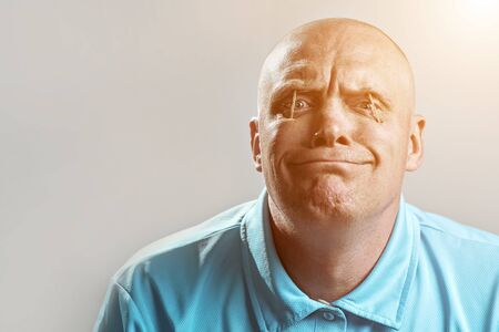 a bald brutal man in a light t-shirt put matches in his eyes and sleeps Stock Photo
