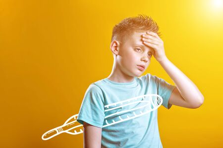 sick boy in a light t-shirt measures the temperature of a thermometer on a colored background