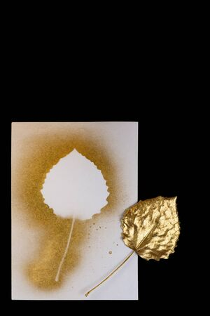 autumn composition of gold leaf and postcards on a black background Stock Photo