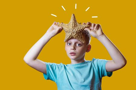 a boy in a light t-shirt holding a starfish on a bright yellow background Фото со стока