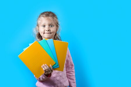 Cute cheerful girl with dimples on her cheeks and curly hair holding colorful school notebooks on a blue background