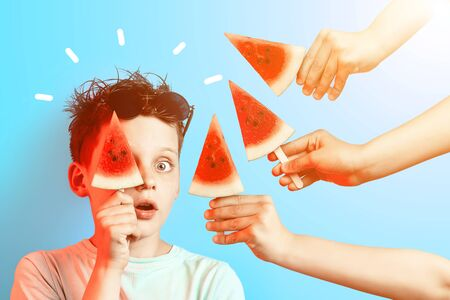 boy in light t-shirt watermelon on a stick closes one eye on a blue background