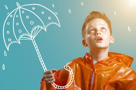 a boy in an orange raincoat and with a painted umbrella stands in the rain