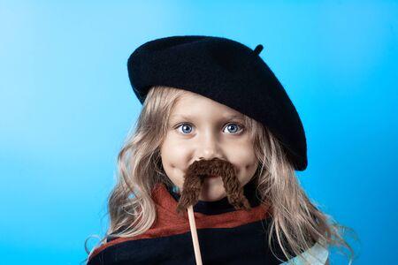 Chica divertida en boina negra, bufanda y bigote en un palo sobre un fondo azul.