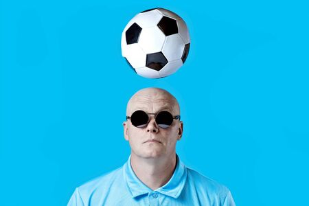 bald brutal man in dark round glasses with highlights. A football hovered overhead. Blue background.