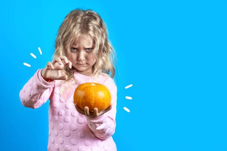 cute witch girl with blonde hair conjures over a pumpkin on a colored background