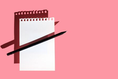 a blank sheet of Notepad, black pencil and hard shadows on a bright pink background