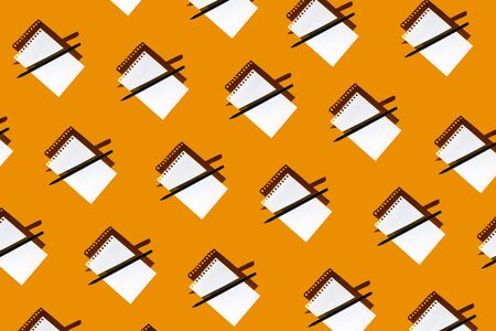 a pattern of blank Notepad, black pencil and hard shadows on a bright yellow background Banque d'images