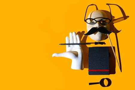 composition of various objects. Glasses, magnifying glass, pencil, mustache, butterfly, hand, notebook, mask. Form the image of a business person. Hard shadows on yellow background