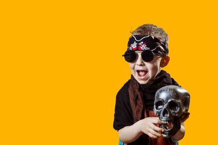 boy rocker in black glasses, scarf, bandana and with a skull in his hands on a bright background 写真素材