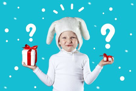a boy dressed as a white hare tries to choose a gift on blue background