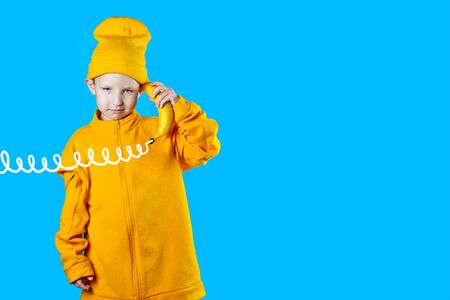 A cool boy in a bright yellow jacket and hat holds a banana in his hands like a phone. On blue background