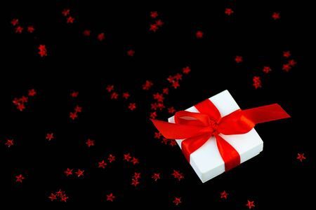 White gift box with a red ribbon and a scattering of stars on a black background.