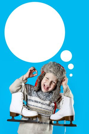 cheerful boy in a hat with earflaps holding ice skates on a blue background