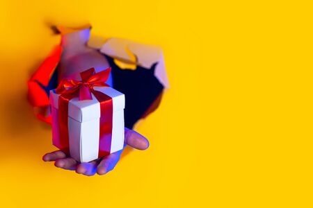 A gift with a red bow in hand emerges from a ragged hole in a yellow paper background, illuminated by neon light Stock Photo