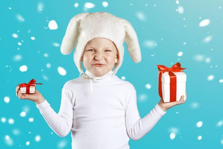 a boy dressed as a white hare tries to choose a gift on a blue background