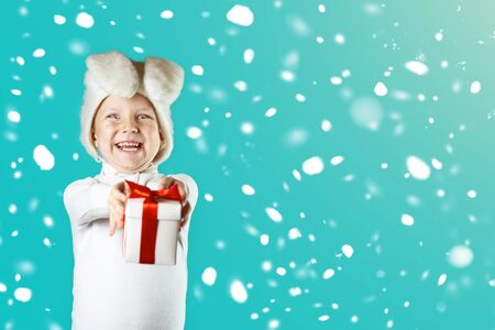 A cheerful boy in a white hare costume gives a gift with a red ribbon on a mint background. Snow is falling Imagens