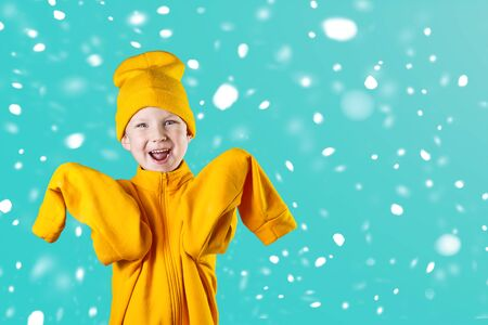 A cheerful guy in a bright yellow jacket and hat enthusiastically rejoices on a mint background
