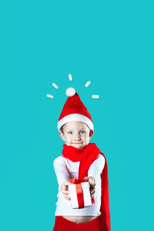 little cheerful Santa gives a gift on a mint background