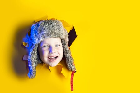a small cheerful child in a winter hat with earflaps smiles from a hole in a yellow cardboard background Zdjęcie Seryjne