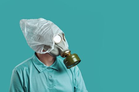 a man in a gas mask and a plastic bag on his head symbolizes the protection of the environment from pollution on mint background
