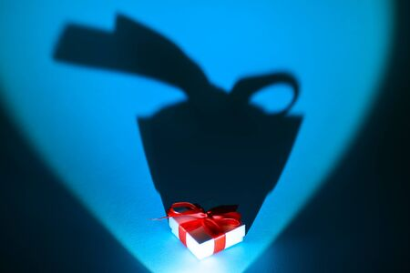 white box with a gift and a bow on blue background with a long shadow