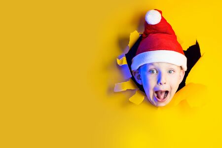 little cheerful Santa in a hat smiles, getting out of the ragged yellow background lit by neon light
