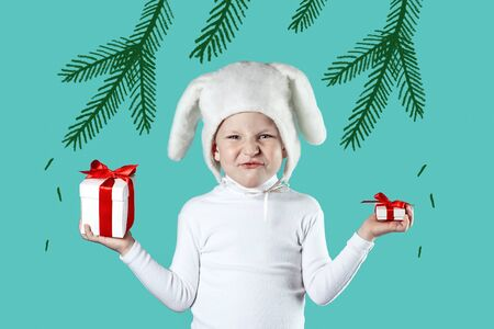 a boy dressed as a white hare tries to choose a gift on a mint background and fir branches Imagens