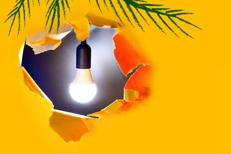 Concept of creative idea. A light bulb shines in a hole of yellow paper