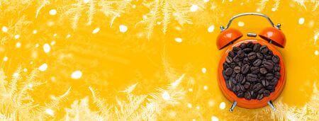 coffee beans in orange alarm clock on bright yellow background Stock Photo