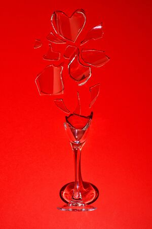 A broken glass on a red background. It's a hard shadow. One shard is like a heart.