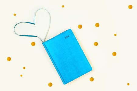 Blue diary and golden rounds. On a light background. Heart-shaped bookmarks Standard-Bild