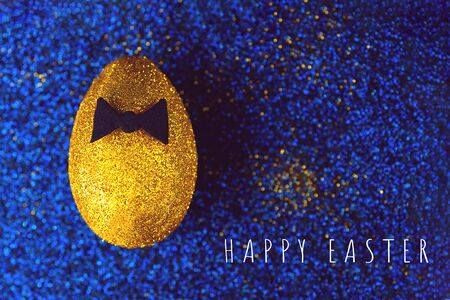 Golden egg on a blue textured background. With a bow tie. The concept on the theme of Easter.