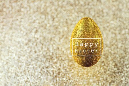 A golden egg hangs in the air. On a textured gold background. The concept on the theme of Easter.