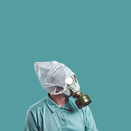 a man in a gas mask and a plastic bag on his head symbolizes the protection of the environment from pollution on a mint background Foto de archivo