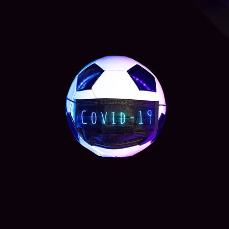 A soccer ball in a black medical mask from the virus. In the light of neon on a dark background. Stock Photo