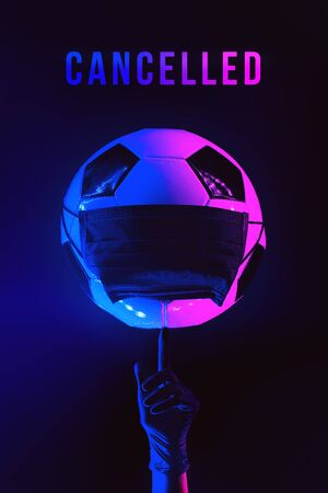 A soccer ball in a black medical mask from the virus. Hand in glove with finger raised. In the light of neon on a dark background.