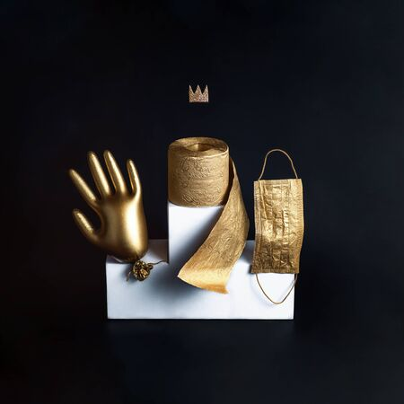 Gold glove, toilet paper and a sanitizer on a white bollard. Concept on the theme of coronavirus trends. Black background Stockfoto - 146285226