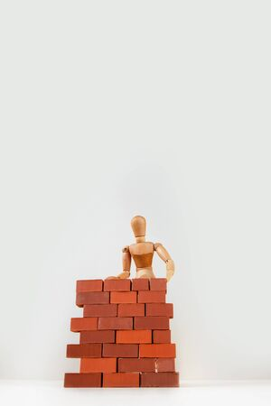 A wooden man builds a brick wall around him. Concept on self-isolation and coronavirus.