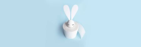 White egg with hare ears in a roll of toilet paper. Hard shadow on a light background. Concept on Easter 2020