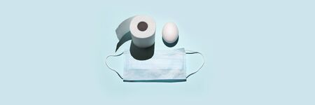 Toilet paper and egg instead of eyes. A medical mask. Concept on the theme of Easter and coronavirus.