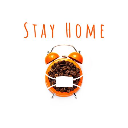coffee beans in orange alarm clock in mask on white background. Pandemic concept Stockfoto