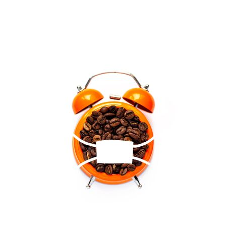 many coffee beans in orange alarm clock in mask on white background