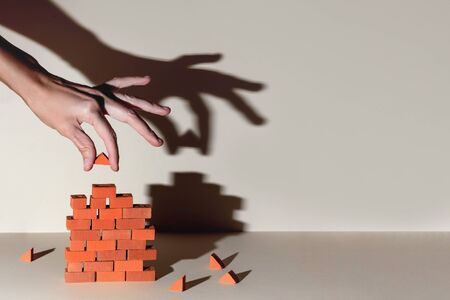 A wooden man builds a brick wall around him. Concept on self-isolation and coronavirus Stockfoto