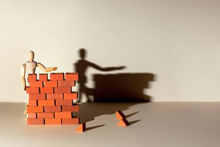 A wooden man builds a brick wall around him. Concept on self-isolation and coronavirus Stockfoto - 146285232