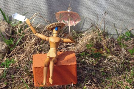 A wooden man sits on a brick under an umbrella after the quarantine is lifted. He threw off his mask and began to sunbathe. Concept on the topic of the pandemic Stockfoto