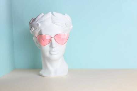 White sculpture of an antique head in pink glasses with hearts. On a geometric background of two colors Stockfoto - 147269385