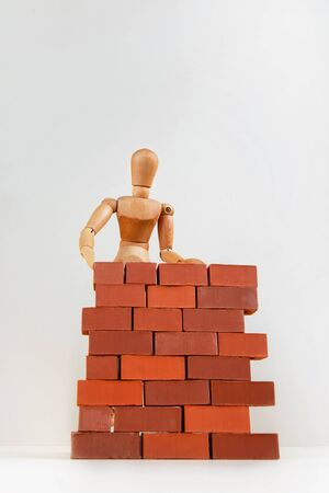 A wooden man builds a brick wall around him. Concept on self-isolation and coronavirus. Stockfoto - 147269393
